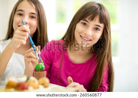 Twins girls decorating Easter eggs together - stock photo