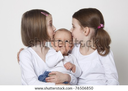 Twins sisters with baby boy brother on white background - stock photo