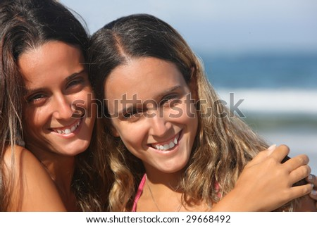 twins smiling in the beach - stock photo