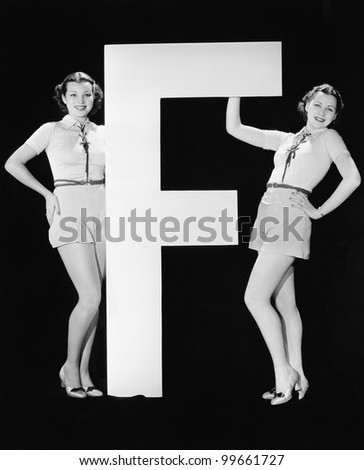 Twins with huge letter F - stock photo