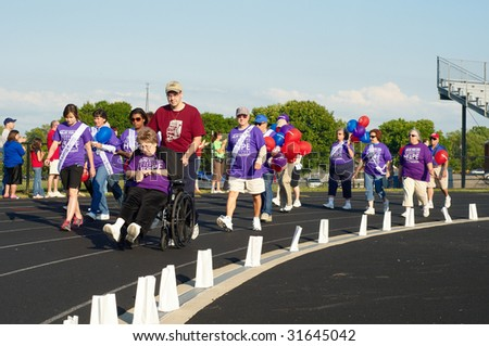 TWINSBURG, OH - June 5: Cancer survivors walk the first lap of Relay for Life, an annual fundraising event sponsored by the American Cancer Society, June 5, 2009, in Twinsburg, Ohio. - stock photo