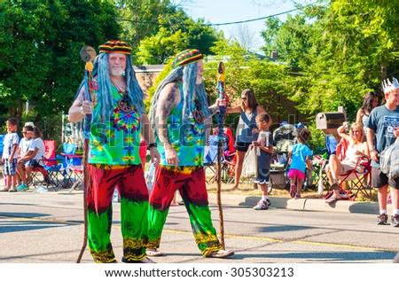 TWINSBURG, OH, USA - AUGUST 8, 2015: Twin brothers dressed in colorful hippie attire walk in the Double Take Parade at the 40th annual Twins Day festival, the largest gathering of twins in the world. - stock photo