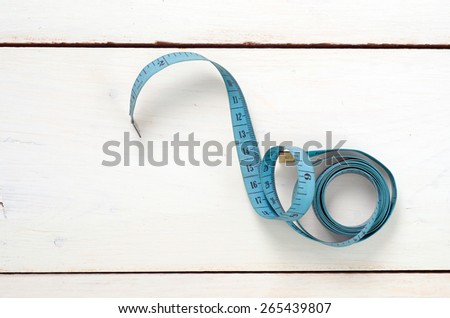 twisted tape measure on white background - stock photo