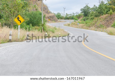 Twisty mountain road with roadsign in nature - stock photo