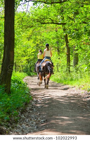 Two a young girls on horseback riding in the route - stock photo