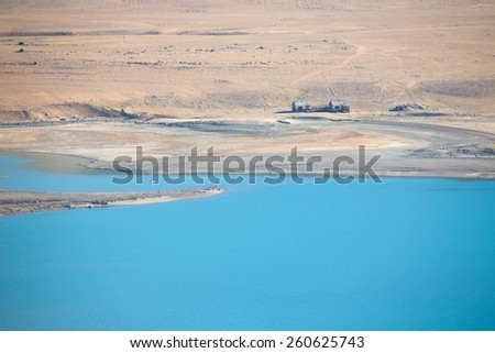 Two abandoned houses on the shore of a clean mountain lake in a dry rocky valley. Toned. - stock photo