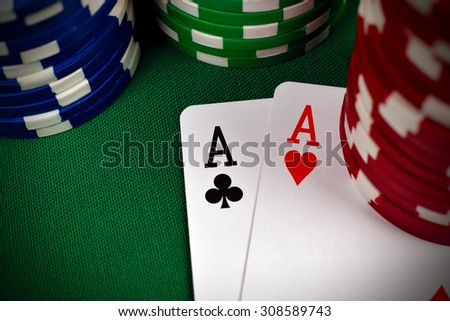 two aces, including spades, hearts, clubs and  poker chips - stock photo