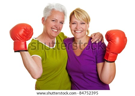 Two active senior women with red boxing gloves - stock photo