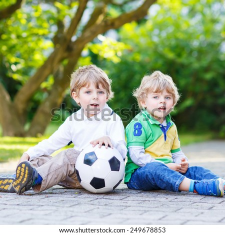Two active twins playing soccer and football and having fun, outdoors. Active leisure with children on warm sunny summer day. - stock photo