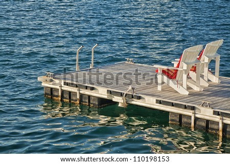 Two adirondack chairs on a floating dock. - stock photo