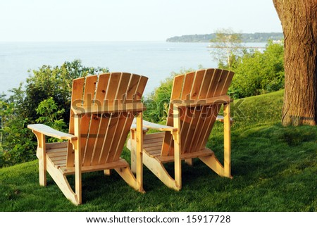 two adirondack chairs on a hillside overlooking a large lake stock