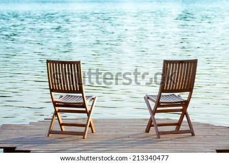 Two adirondack wooden chairs on dock facing a blue lake - stock photo