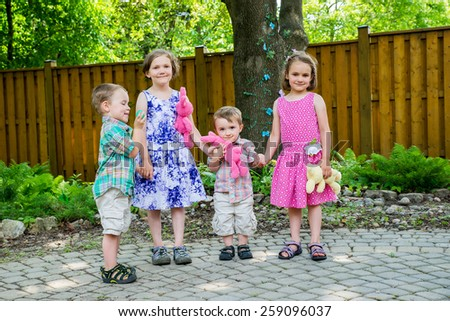 Two adorable boys and happy girls smile holding colorful toy plush bunny rabbits and egg hold hands together during an Easter party outside in a garden.  Part of a series. - stock photo