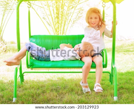 Two adorable child spending leisure time on swing, having fun in summer camp, active holidays, happiness and friendship  concept - stock photo