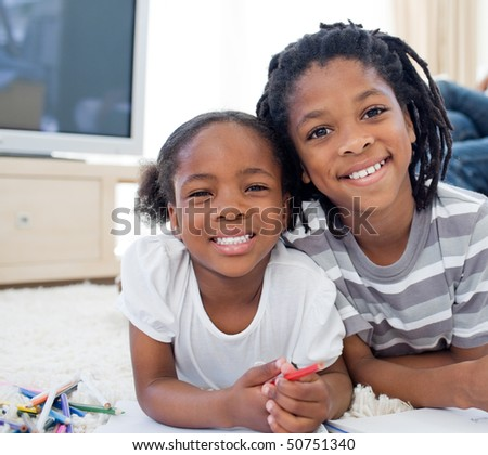 Two adorable children drawing lying down on the floor in the bedroom - stock photo