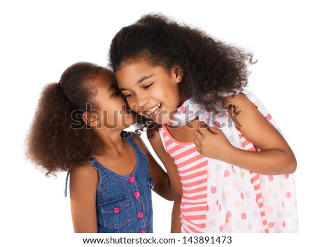 Two adorable cute african children with afro hair. One is wearing a white and pink striped dress and the other a denim dress. They are whispering to each other. - stock photo