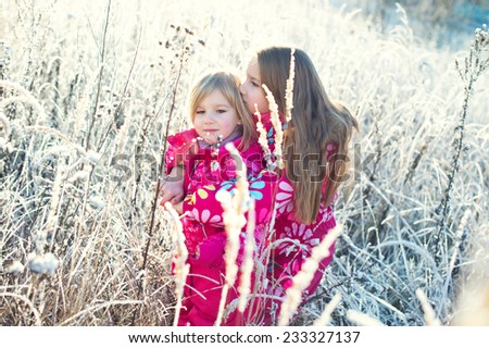 Two adorable european sister girls in colorful clothes holding each other in winter cold field with snow on grass - stock photo