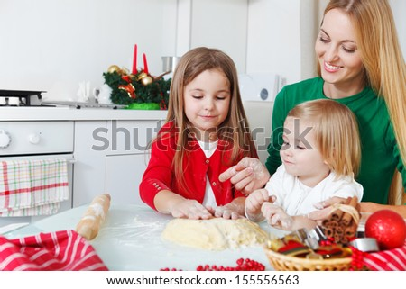 Two adorable girls with her mother baking Christmas cookies in the kitchen - stock photo