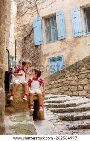 Two adorable kids, sitting on the street rock, smiling, eating ice cream, looking at each other - stock photo