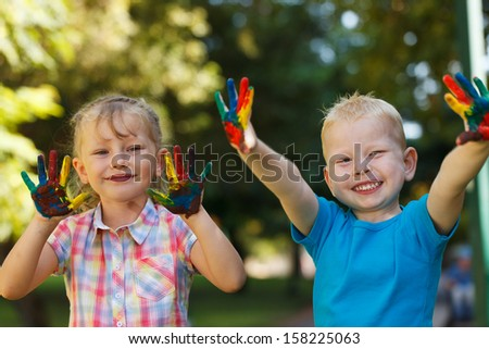 Two adorable kids with hands covered in paint - stock photo