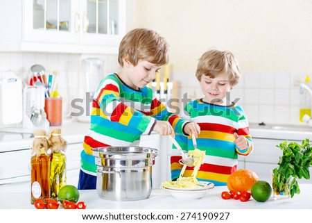 Two adorable little boys cooking and eating meal with spaghetti and fresh vegetables in domestic kitchen, indoors. Sibling children in colorful shirts. - stock photo