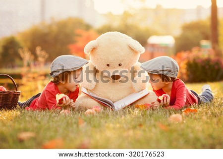 Two adorable little boys with teddy bear friend in the park on sunset, nice back light - stock photo