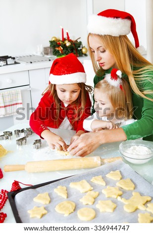 Two adorable little girls and mother baking Christmas cookies in the kitchen - stock photo
