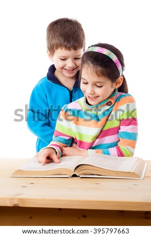 Two adorable little kids reading the book together, isolated on white - stock photo
