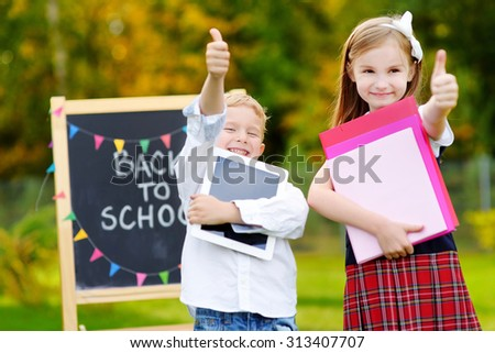 Two adorable little schoolkids feeling very exited about going back to school - stock photo
