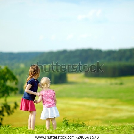 Two adorable little sisters enjoying a beautiful view together on warm and sunny summer day - stock photo