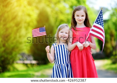 Two adorable little sisters holding american flags outdoors on beautiful summer day. Independence Day concept. - stock photo