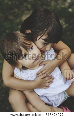Two adorable little sisters  hugging each other  - stock photo