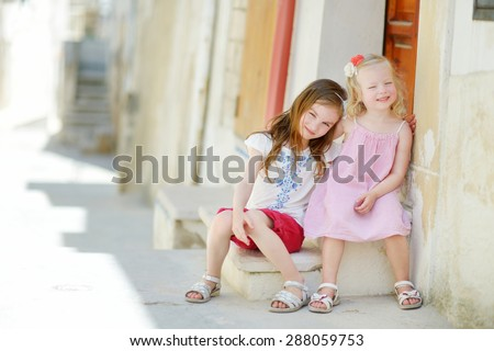 Two adorable little sisters laughing and hugging on warm and sunny summer day in Vieste, Italy - stock photo