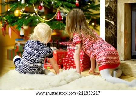 Two adorable little sisters looking for gifts under a Christmas tree on Christmas eve at home - stock photo