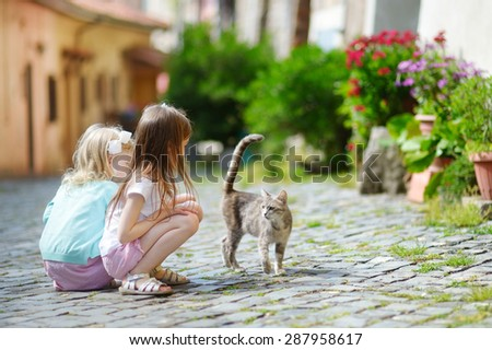 Two adorable little sisters met a cat while walking narrow streets ot typical italian town - stock photo