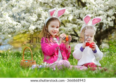 Two adorable little sisters playing with Easter eggs in blooming spring garden on Easter day - stock photo