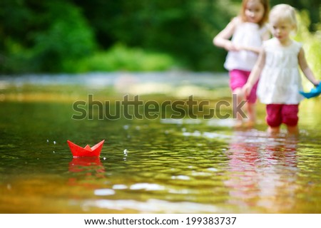 Two adorable little sisters playing with paper boats in a river - stock photo