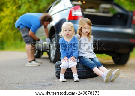 Two adorable little sisters sitting on a tire and waiting while their father is changing a car wheel outdoors on beautiful summer day - stock photo