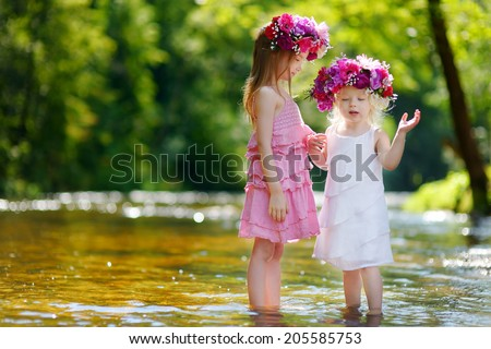 Two adorable little sisters wearing flowers crowns by a river on warm and sunny summer day - stock photo