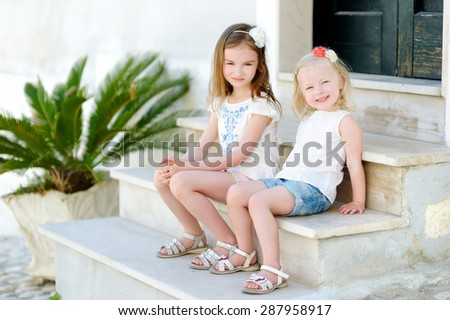 Two adorable little sistershaving fun together on warm and sunny summer day in italian town - stock photo