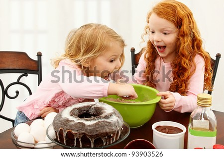 Two adorable preschool sisters mixing batter at kitchen table. - stock photo