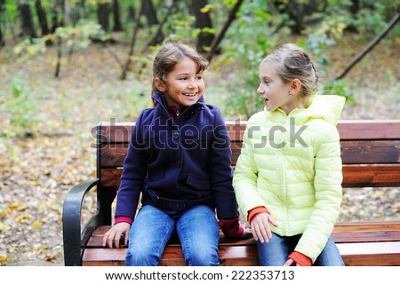 Two adorable preteen girls sitting on a bench  in autumn park - stock photo