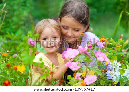 Two adorable sisters among the flowers. Sunny summer day - stock photo