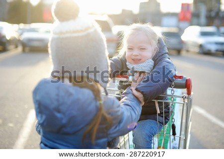 Two adorable sisters playing at parking lot with a shopping cart at cold autumn day - stock photo