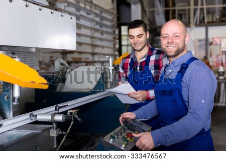 Two adult men working on a factory cutting aluminum frames on a lathe - stock photo