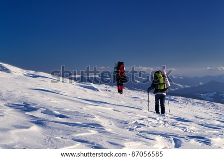 Two adventurers are on the snow slope - stock photo