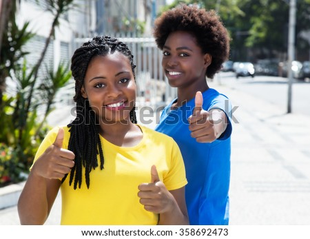 Two african american girlfriends showing thumb up - stock photo