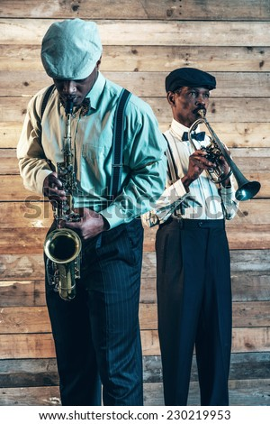 Two african american jazz musicians playing trumpet and saxophone. Standing in front of old wooden wall. - stock photo