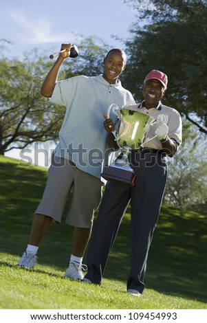 Two African American men holding trophy at golf course - stock photo