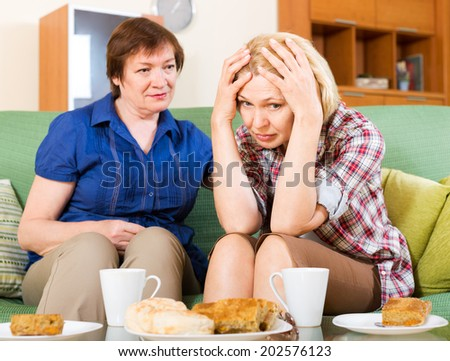 Two aged colleagues drinking tea and discussing working questions - stock photo